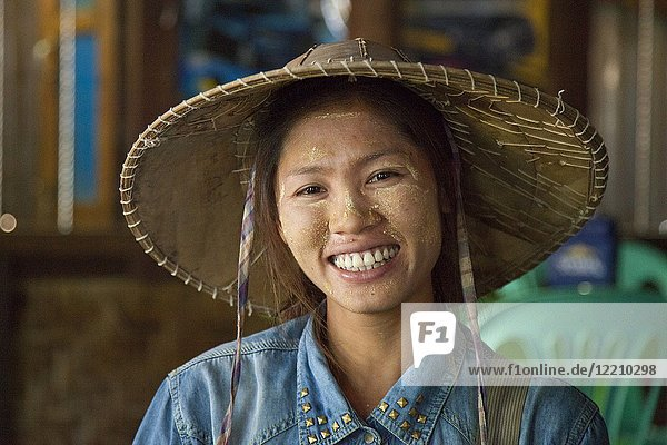 Local Burmese woman with thanaka paste on her face and straw hat selling local crops in Myanmar.