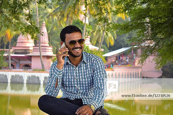 Smiling man sitting on a bench with temple background looking talking on cell phone  Pune  Maharashtra.