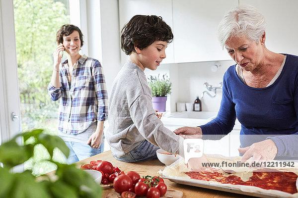 Großmutter und Enkel beim Pizza-Backen in der Küche  Mutter im Hintergrund mit Smartphone