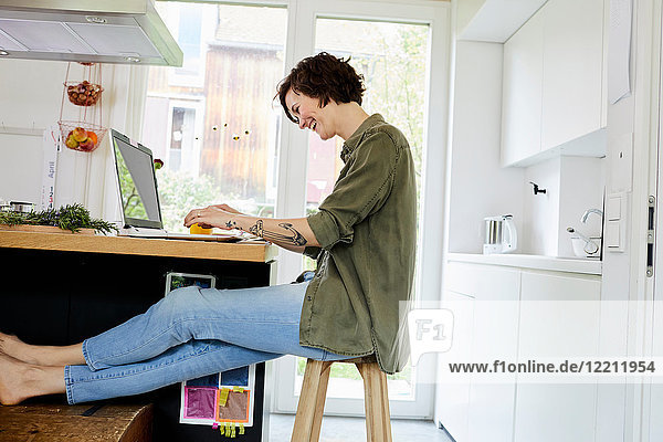Mittlere erwachsene Frau sitzt in der Küche  benutzt einen Laptop und lacht
