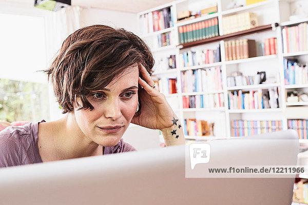 Mittlere erwachsene Frau zu Hause  die einen Laptop benutzt  besorgter Ausdruck