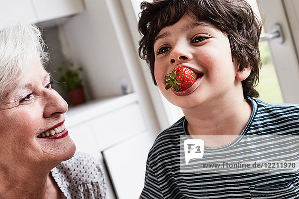Grandson eating strawberry  grandmother sitting beside him  smiling