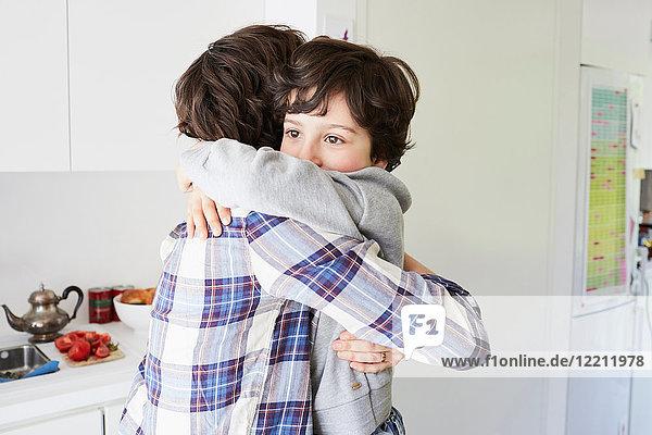 Mutter und Sohn zu Hause  umarmend