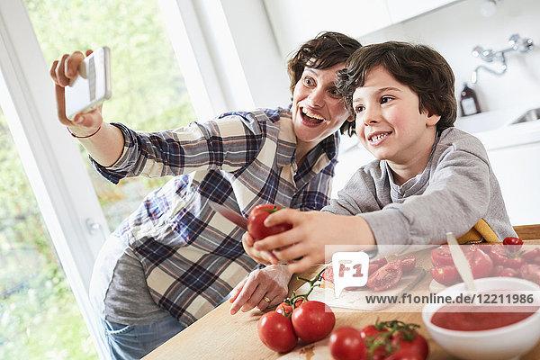 Mutter und Sohn bereiten das Essen in der Küche zu  Mutter nimmt sich selbst mit dem Smartphone