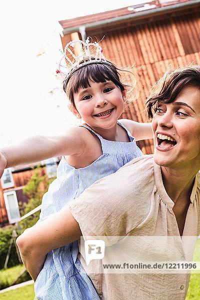 Porträt einer Mutter  die ihre Tochter auf dem Rücken trägt  lächelnd