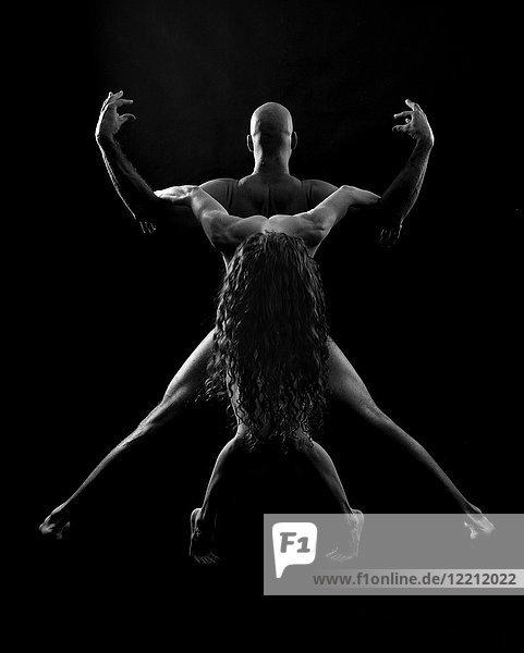 Couple in yoga pose  black background