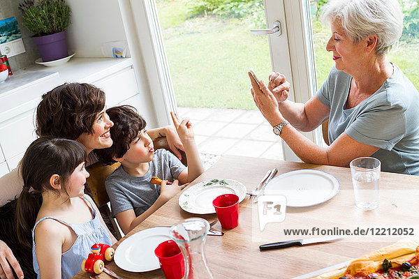 Grandmother sitting at kitchen  photographing grown daughter and grandchildren  using smartphone