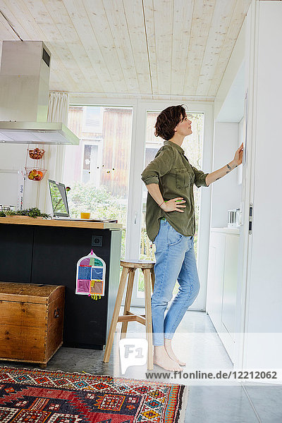 Mid adult woman looking at planner on kitchen wall