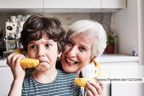 Großmutter und Enkel albern herum  benutzen Bananen als Telefon  lachen