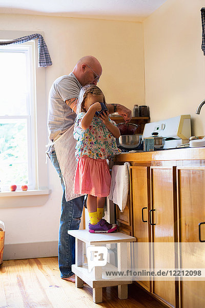 Girl on stool drinking while father prepares food in kitchen