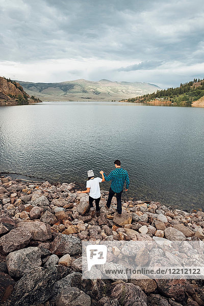 Couple walking on rocks beside Dillon Reservoir  elevated view  Silverthorne  Colorado  USA