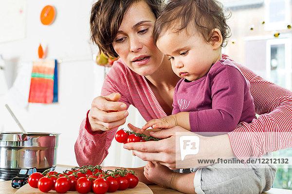Mutter und kleine Tochter in der Küche  Tomaten auf der Küchentheke sortieren