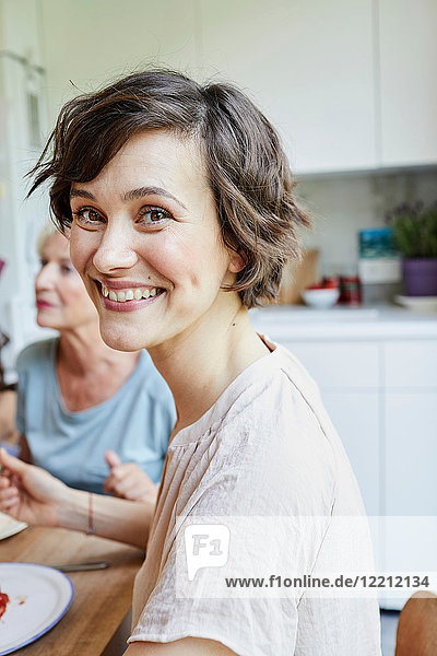 Porträt einer mittleren erwachsenen Frau am Esstisch  lächelnd
