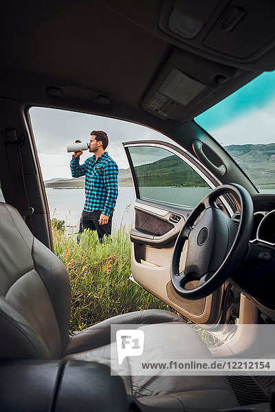 Mid adult man standing beside Dillon Reservoir  drinking from water bottle  view through parked car  Silverthorne  Colorado  USA
