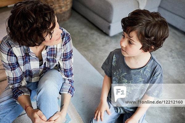 Mutter und Sohn zu Hause  sitzen auf dem Boden und unterhalten sich