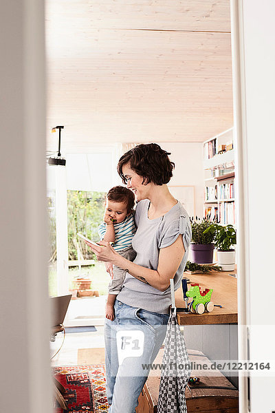 Mother holding baby daughter in kitchen  looking at smartphone