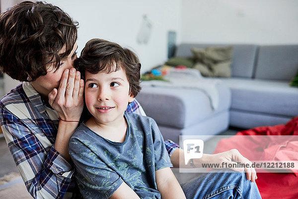 Mutter und Sohn zu Hause  Mutter flüstert dem Sohn ins Ohr