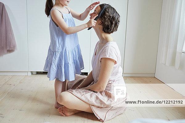 Mutter sitzt auf dem Boden  Tochter bürstet der Mutter die Haare  Mittelteil