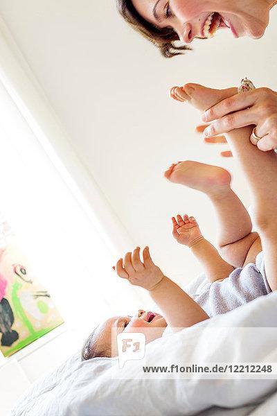 Mutter spielt mit der kleinen Tochter  lacht