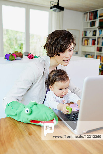 Mother using laptop with baby girl sitting on her lap