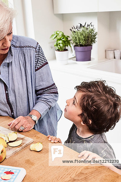 Grandmother and grandson preparing food in kitchen  grandson with questioning expression