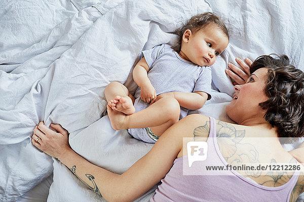Mutter und kleines Mädchen liegen zusammen im Bett