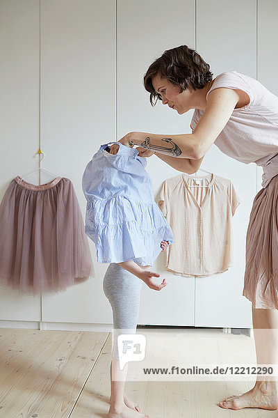 Mutter hilft Tochter beim Anziehen