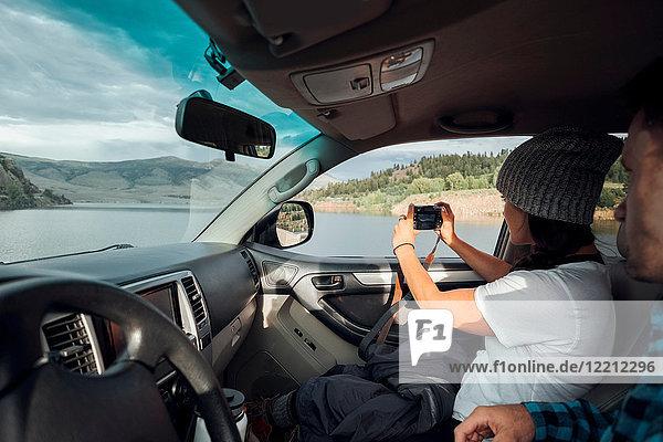 Couple in car  young woman taking photograph through car window  Silverthorne  Colorado  USA