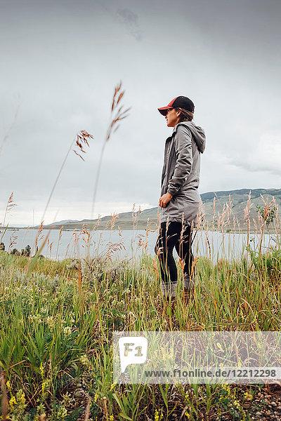 Junge Frau steht in der Nähe des Dillon Reservoirs und schaut auf die Aussicht  Silverthorne  Colorado  USA