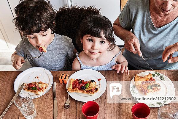 Großmutter sitzt mit Enkelkindern am Küchentisch  isst Pizza  erhöhte Ansicht
