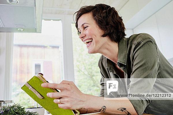MId Erwachsener mit Tätowierungen am Arm  mit digitalem Tablett in der Küche  Mittelteil  lachend