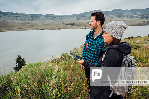 Couple hiking  standing beside Dillon Reservoir  young woman holding digital tablet  Silverthorne  Colorado  USA