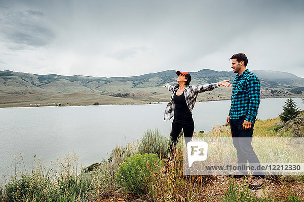 Couple walking near Dillon Reservoir  young woman's arms outstretched  Silverthorne  Colorado  USA