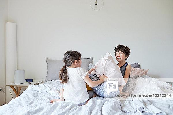 Bruder und Schwester haben Kissenschlacht im Bett
