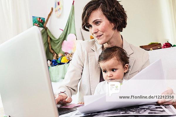 Mutter sitzt sitzend mit der kleinen Tochter und arbeitet am Laptop
