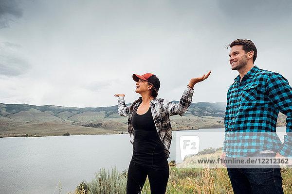 Couple walking near Dillon Reservoir  young woman's arms raised  Silverthorne  Colorado  USA