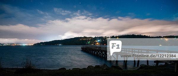 Panoramic image of lights on shoreline across water and pier  Bainbridge  Washington  United States