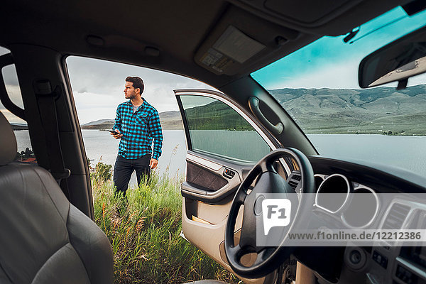 Mid adult man standing beside Dillon Reservoir  holding smartphone  view through parked car  Silverthorne  Colorado  USA