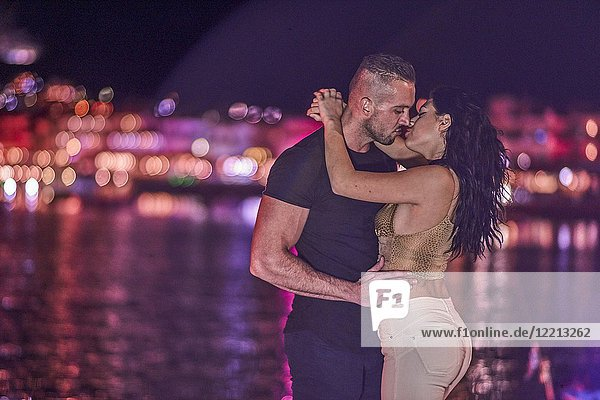 Sensual couple kissing in city lights at harbour at night. Greek ethnicity. In Hersonissos  Crete  Greece.