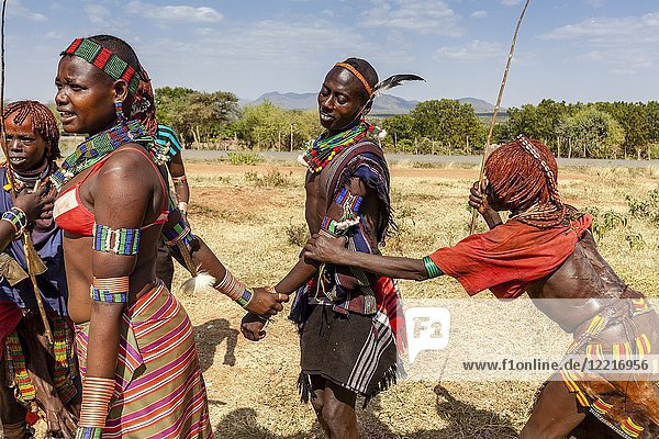 Young Hamar Women Taunt A Hamar Tribesman In To Whipping Them. The Young Women Ask To be Whipped To Show Love For A Family Member Who Is Taking Part In A 'coming of age'. Bull Jumping Ceremony  Dimeka  Omo Valley  Ethiopia.