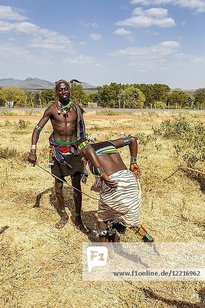A Hamar Tribesman Whipping Young Hamar Women. The Young Women Ask To be Whipped To Show Love For A Family Member Who Is Taking Part In A 'coming of age'. Bull Jumping Ceremony  Dimeka  Omo Valley  Ethiopia.