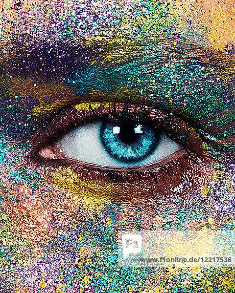 Studioporträt einer blauäugigen jungen Frau mit glitzerndem  mehrfarbigem Puder im Gesicht  Nahaufnahme des Auges