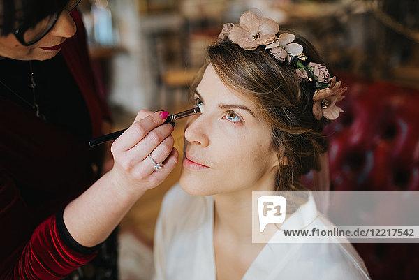 Braut bereitet sich mit Visagistin auf Hochzeit vor