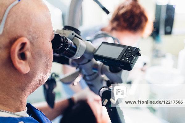 Zahnarzt und Zahnarzthelferin führen Verfahren am Patienten durch