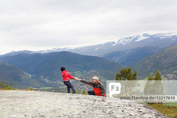 Boy helping hiker father over rock in mountain landscape  Jotunheimen National Park  Lom  Oppland  Norway