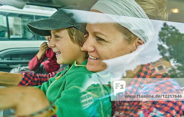 Mutter und Söhne im Fahrzeug  lächelnd  Blick durchs Fenster