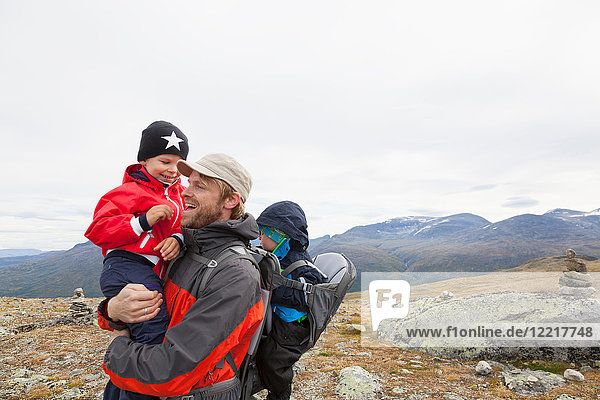 Male hiker with sons in mountain landscape  Jotunheimen National Park  Lom  Oppland  Norway