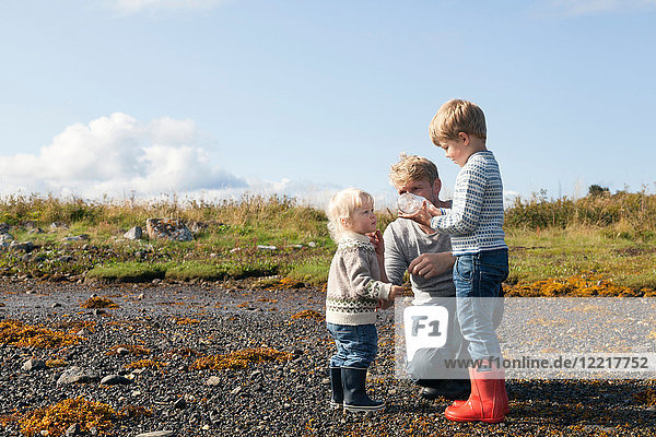 Mann mit Sohn schaut in Flasche am Strand  Aure  More og Romsdal  Norwegen