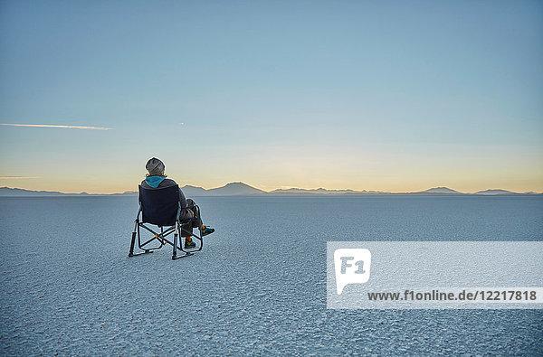 Frau sitzt im Campingstuhl  auf Salinen  Blick auf Aussicht  Salar de Uyuni  Uyuni  Oruro  Bolivien  Südamerika