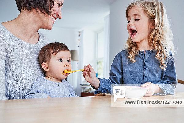 Familie sitzt am Küchentisch  junges Mädchen füttert Babyschwester mit einem Löffel